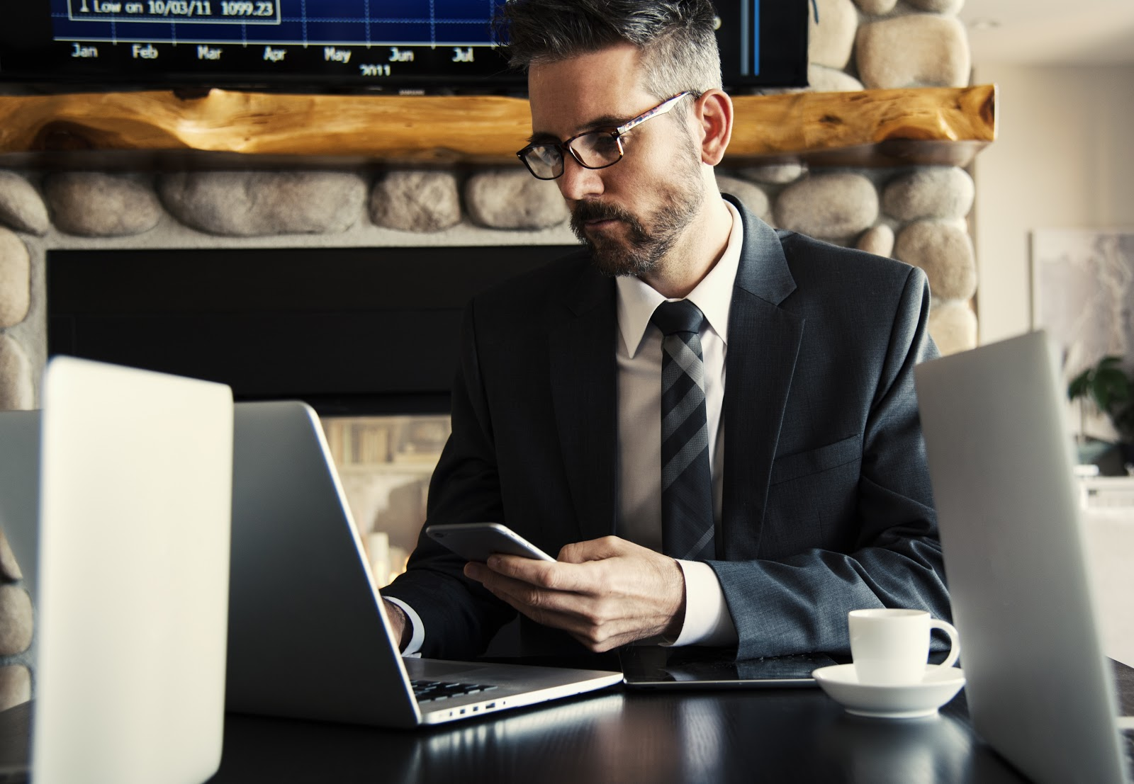 Professional man in suit using smartphone and laptop